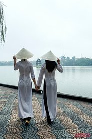 Young vietnamese girls in traditional Ao Dai dress walking near lake