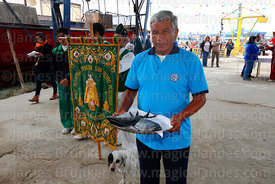 Man carrying offering of fish to altar before holy communion during mass for St Peter and St Paul festival, Arica, Chile