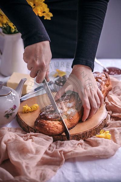 Woman slicing Braided sweet Easter bread served for breakfast with butter and jam