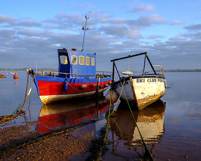 Boats moored on the shoreline of the calm Exe Estuary, Exmouth, Devon, UK