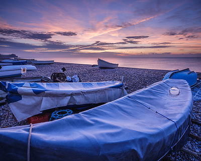 Frosty fishing boat covers and vivid dawn sky on the pebbled beach at Budliegh Salterton, Devon, UK