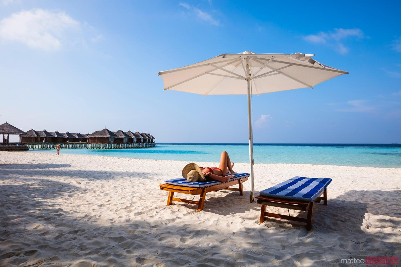 Woman relaxing on lounge chair, Maldives