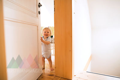 Portrait of happy baby boy opening the door