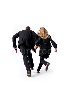 A man and a woman running hand in hand, from behind – shot from mid level.