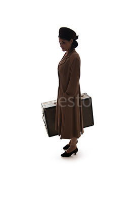 A silhouette of a 1940's woman in a hat and coat, carrying a suitcase – shot from eye-level.