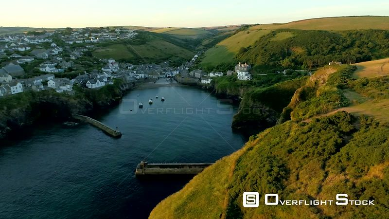 Drone flies sideways from cliffs with the village of Port Isaac behind in the golden light of dawn