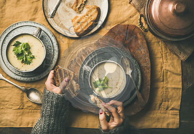 Celery cream soup and female hands with grilled bread
