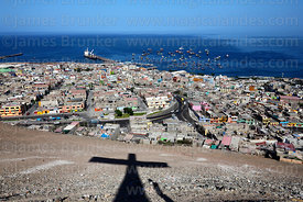 Shadow of cross on hillside overlooking the town and port of Ilo, Peru