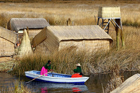 Aymara girls in rowing boat , Uros floating reed islands , Lake Titicaca , Peru