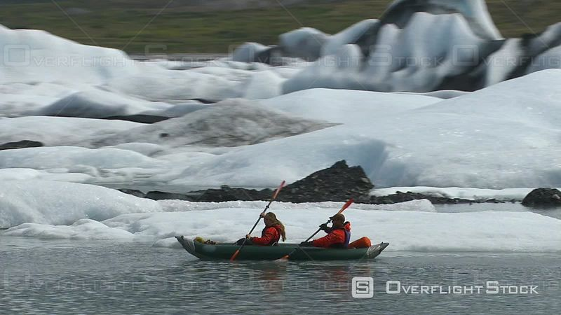 Couple Kayaking by Icebergs and Glacier, Alaska