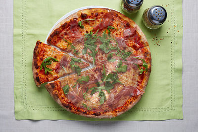 Gourmet wood fired proscuitto and arugula pizza photographed from above on a linen surface with chili flakes and herbs.