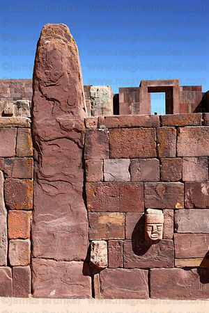 Stone heads on wall of Sunken Temple, Kalasasaya temple entrance in background, Tiwanaku, Bolivia