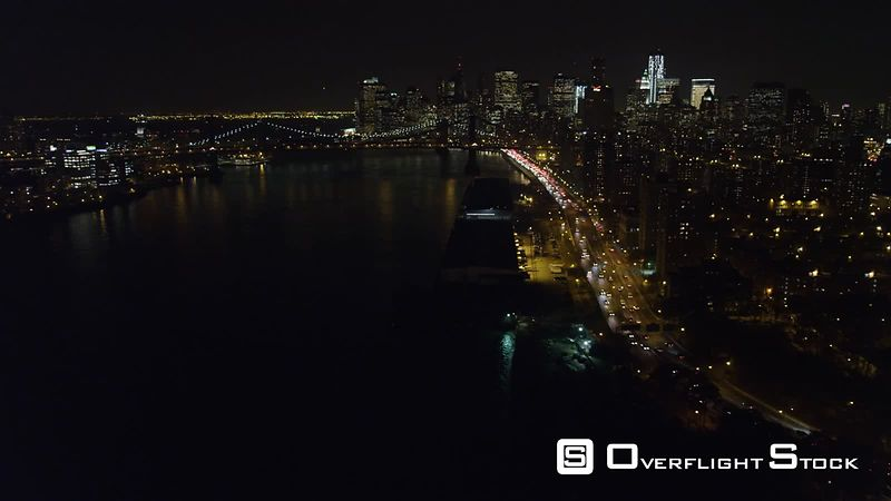 Flying above the East River toward the Manhattan Bridge at night.