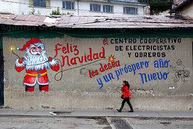 Woman walking past Father Christmas mural on wall of the offices of an electricians and electrical workers cooperative, La Paz, Bolivia