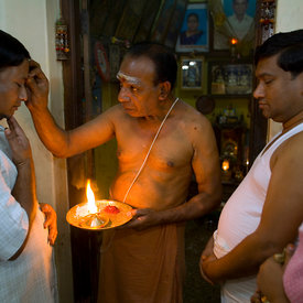 The family priest gives a blessing to Radakrishna and Srikanda Stpathy and their wives in the family shrine in the Stapathy house