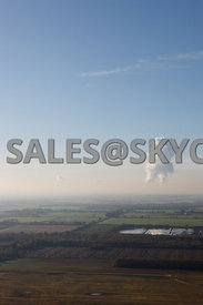 Aerial photograph of farmland with Fiddlers Ferry power station  on the horizon with steam plumes rising above the station set against a blue cloud free sky
