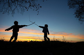 Young children playing having a stick fight on edge of woodland at sunset Norfolk December