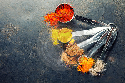 Colorful spices in metal spoons