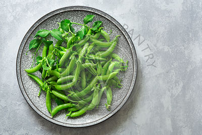 Freshly picked organic sugar snap peas on a plate.
