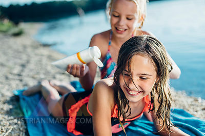 Portrait of laughing girl on the beach with her friend