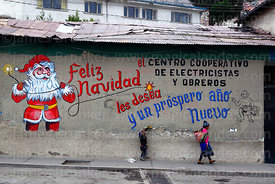 Children walking past Father Christmas mural on wall of the offices of an electricians and electrical workers cooperative, La Paz, Bolivia