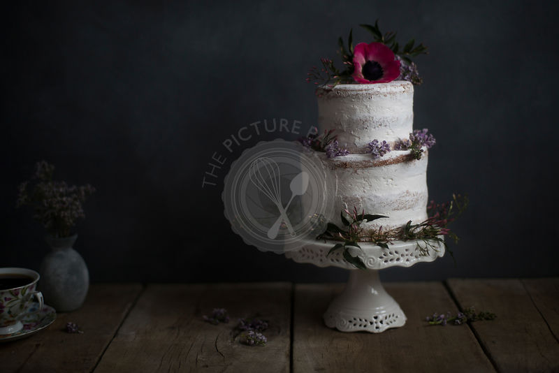 Homemade cake, flower decorated, on a stand. Dark background.