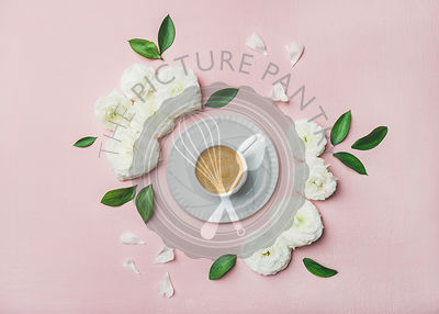 Flat-lay of cup of freshly brewed coffee surrounded with white ranunculus flowers and petals over light pink pastel background