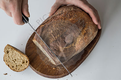 Hands cutting rustic loaf on wooden board and white tabletop with cut slices. Top view