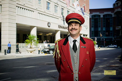 Portrait of a bellman standing in front of a luxury hotel.  The bell man is wearing a red uniform.