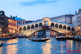 Rialto bridge with gondola at night, Venice, Italy