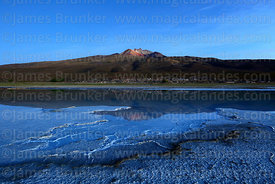 Tunupa volcano reflected in saline pool in pre dawn twilight, Salar de Uyuni, Bolivia
