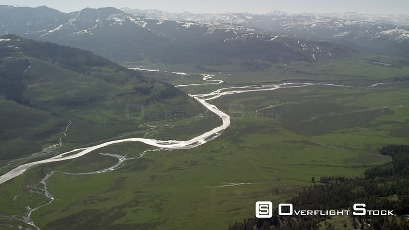 The Lamar River winds through the spring green grass of the Lamar Valley in Yellowstone National Park