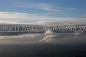 Winter Sky aerial photograph of the Steam Plumes rising from Fiddlers Ferry Power Station Cooling Towers against a background of layers of dark threatening clouds and blue sky