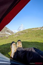 Hiker looking at the Martterhorn from inside a camping tent