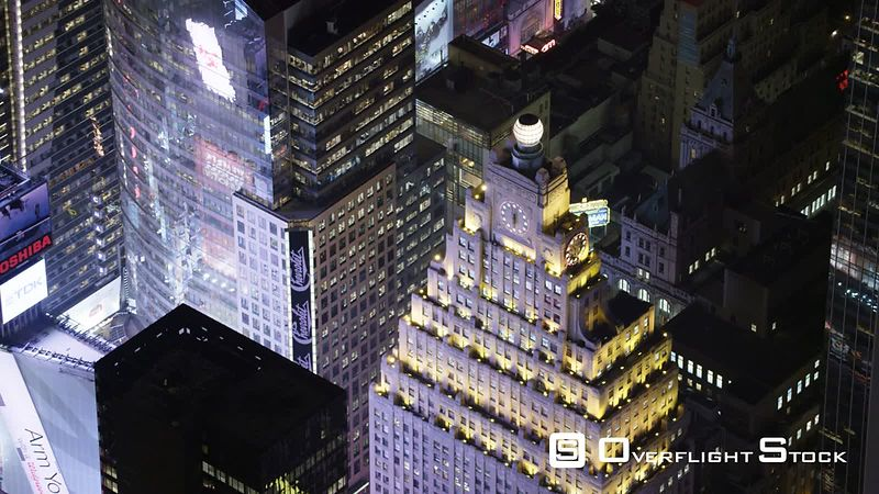 Flying close over buildings near Times Square at night, looking back.