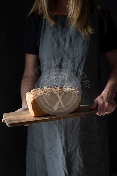 Baked bread in a rustic kitchen, held by a woman