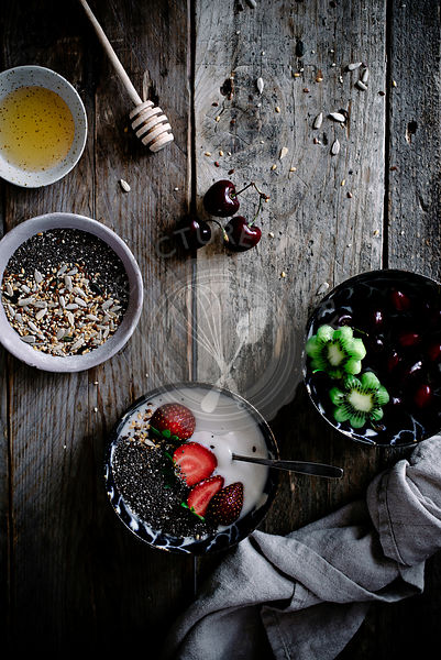 Healthy yoghurt, chia and fruit for breakfast, on a rustic kitchen table.