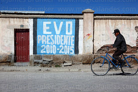 Man cycling past pro Evo Morales mural on house, Uyuni, Bolivia