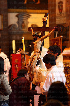 Quechua devotee kisses feet of crucified Christ during Good Friday mass in La Merced church , Cusco , Peru