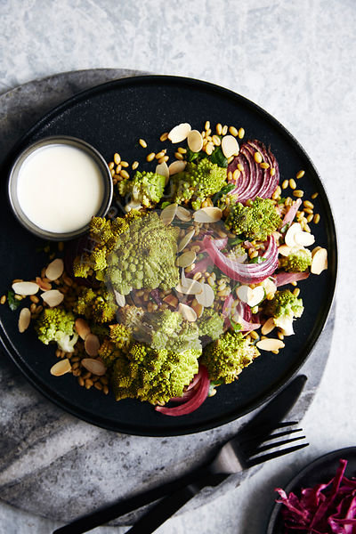Roasted romanesco cauliflower salad with roasted red onions and ancient grains (roasted farro). garnished with toasted almonds and a lemon yogurt sauce. side of picked red cabbage.