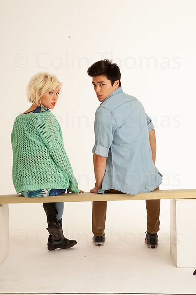 Teenage boy and girl sitting back view photos