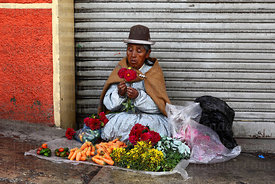 Aymara woman selling flowers and carrots in street market , La Paz , Bolivia