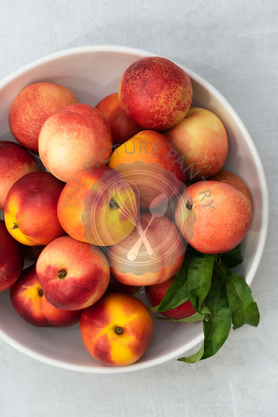 Whole red and yellow nectarines in a bowl.