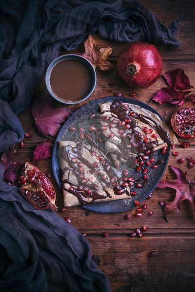 Crepes with melted dark chocolate drizzle and pomegranate seeds