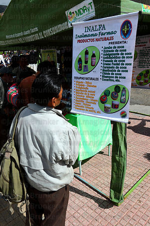 Man reading about coca based medicinal products at stall at trade fair promoting alternative products made from coca leaves , La Paz , Bolivia