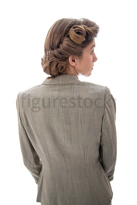 A 1940's / 1950's  woman in a suit, standing, looking away.