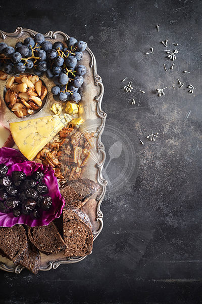 Charcuterie tray with grapes, cheeses, nuts, roasted garlic, olives and toast on a festive metal tray on a dark rustic surface.