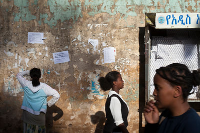 Ethiopia - Addis Ababa - A woman looks at a poster advertising jobs on the street