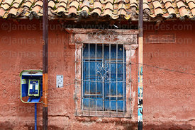 Public payphone and window of colonial house, Lampa, Peru