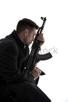 A Figurestock image of a emotional / tired young man in a long black winter coat, with an AK47 – shot from mid level.